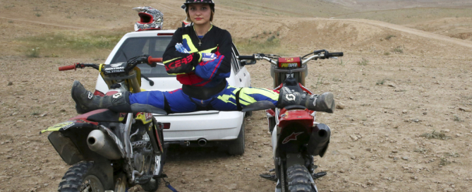 "In this photo taken Sunday, May 31, 2015, Iranian motocross rider Behnaz Shafiei poses for a photo as she stretches her legs, while a male rider takes to the air at a racetrack at a sports complex on the outskirts of Hashtgerd, some 45 miles (73 kilometers) west of the capital Tehran, Iran. ""My goal is to be a pioneer to inspire other women,"" she said. ""Together, we can convince authorities to recognize women's motorcycle racing."" (AP Photo/Vahid Salemi)"